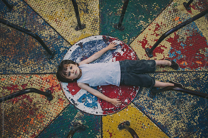 Above Shot of Young Boy Laying on an Old Playground by Kevin Keller for Stocksy United