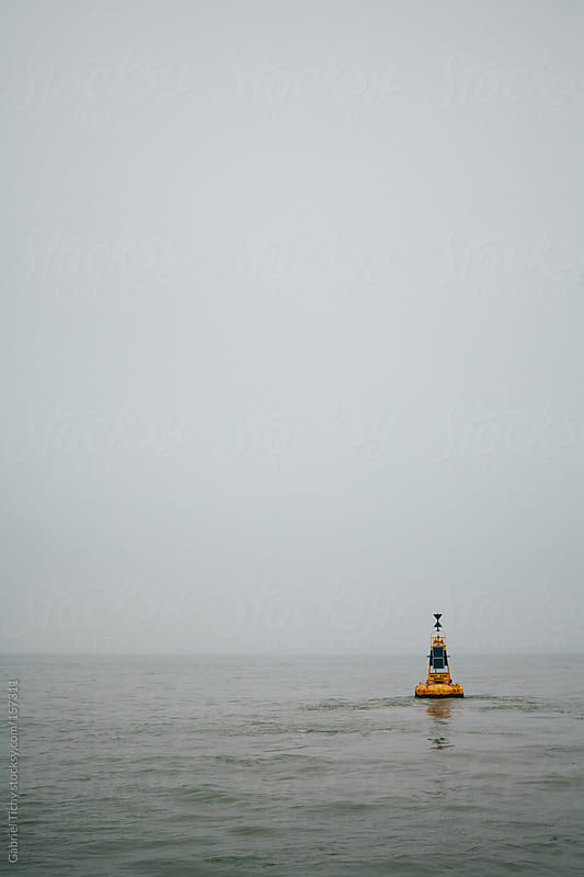 Yellow buoy floating in sea by Gabriel Tichy for Stocksy United
