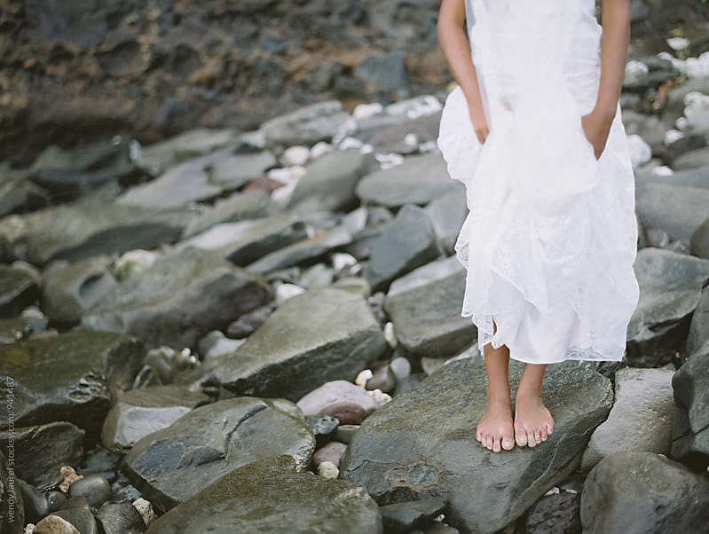 beautiful black bride on beach in gorgeous wedding gown with rocks and ocean by wendy laurel for Stocksy United