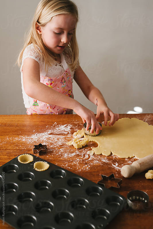 A little girl baking by Helen Rushbrook for Stocksy United