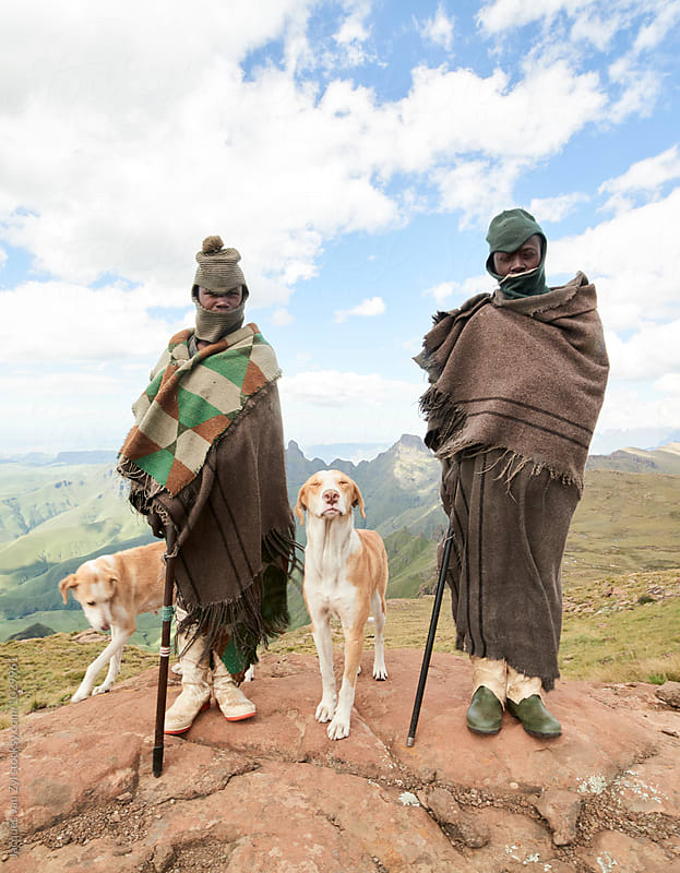 Two Basotho shepherds and their dogs standing on a cold mountain cliff edge, dressed in traditional blankets and walking sticks in a cloudy mountainous landscape. by Jacques van Zyl for Stocksy United