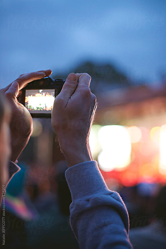man photographing a band with small camera at a music festival by Natalie JEFFCOTT for Stocksy United