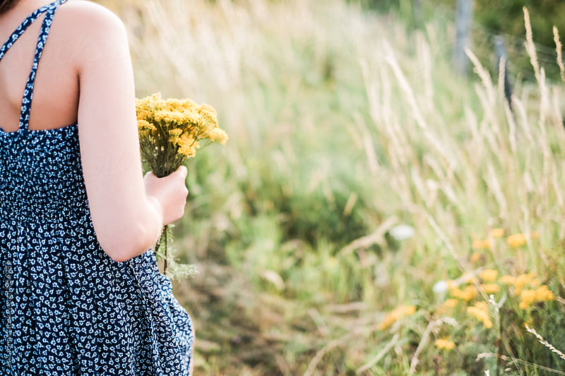 Young woman picking yellow flowers by Léa Jones for Stocksy United