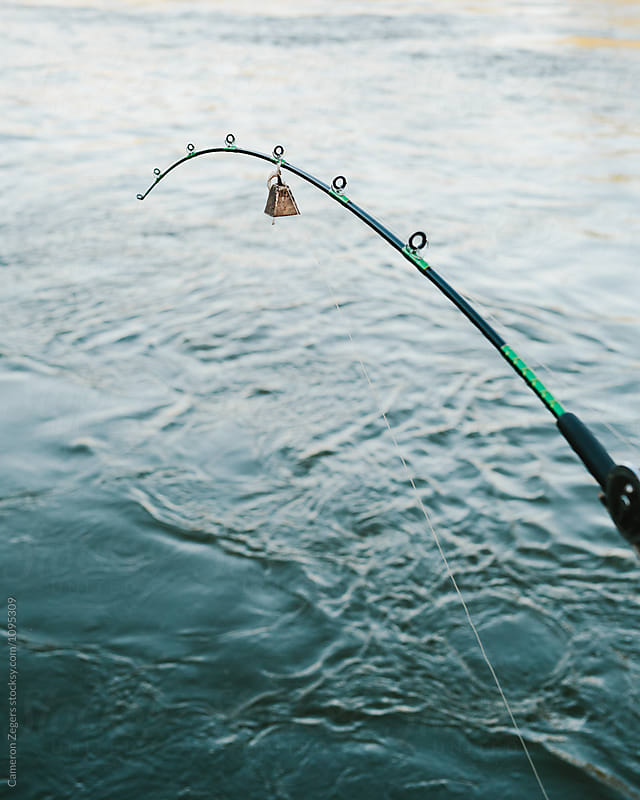 fishing pole and river water by Cameron Zegers for Stocksy United