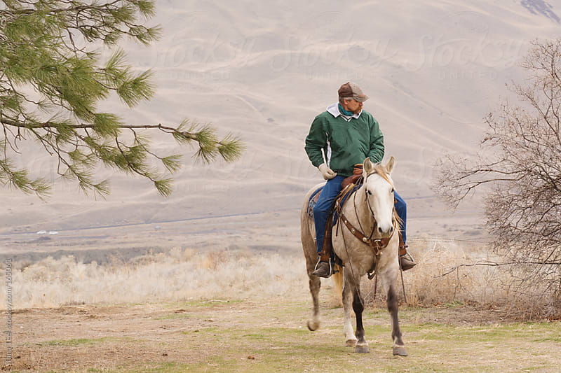A man and his horse riding in the country by Tana Teel for Stocksy United