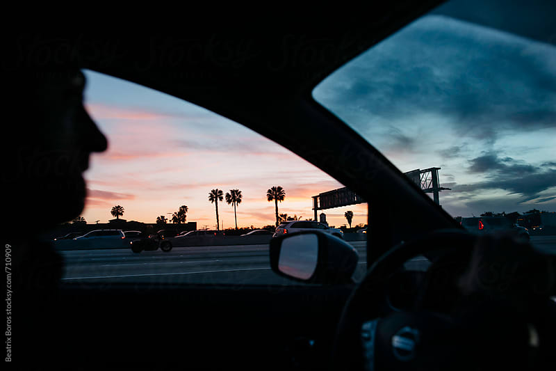 Man driving a car at dusk by Beatrix Boros for Stocksy United