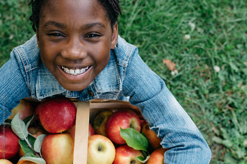 Smiling black girl with apple basket by Gabriel (Gabi) Bucataru for Stocksy United