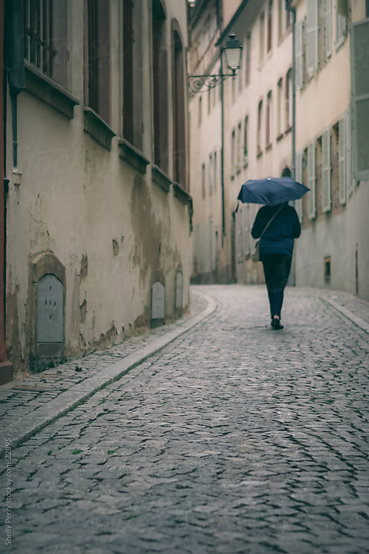 Woman walks away down a cobbled path under an umbrella in France by Shelly Perry for Stocksy United