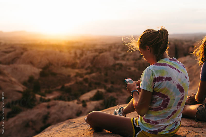 Woman Texting in Desert Sunset by Willie Dalton for Stocksy United