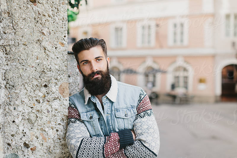 Handsome bearded man leaning against a wall by Amir Kaljikovic for Stocksy United