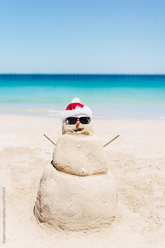Sand snowman wearing sunglasses at the beach on Christmas day in Australia by Angela Lumsden for Stocksy United