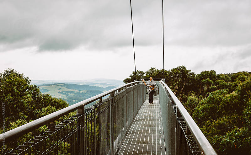 Woman staying on footbridge over the forest by Trent Lanz for Stocksy United