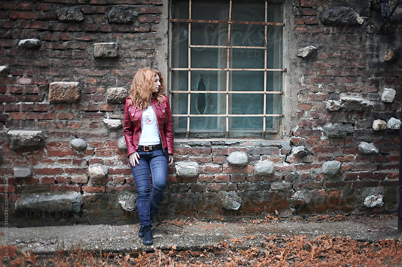 Young beautiful blond woman standing in front of a castle by Maja Topcagic for Stocksy United