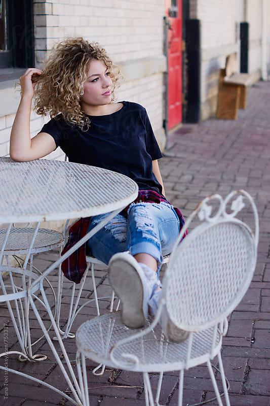 young woman sitting at outside table by Tana Teel for Stocksy United