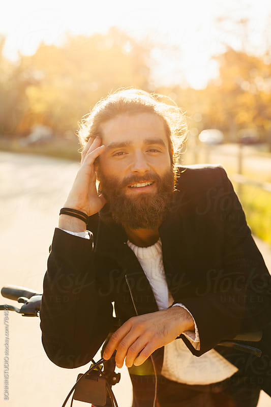 Portrait of a bearded man with his bicycle on a forest road. by BONNINSTUDIO for Stocksy United