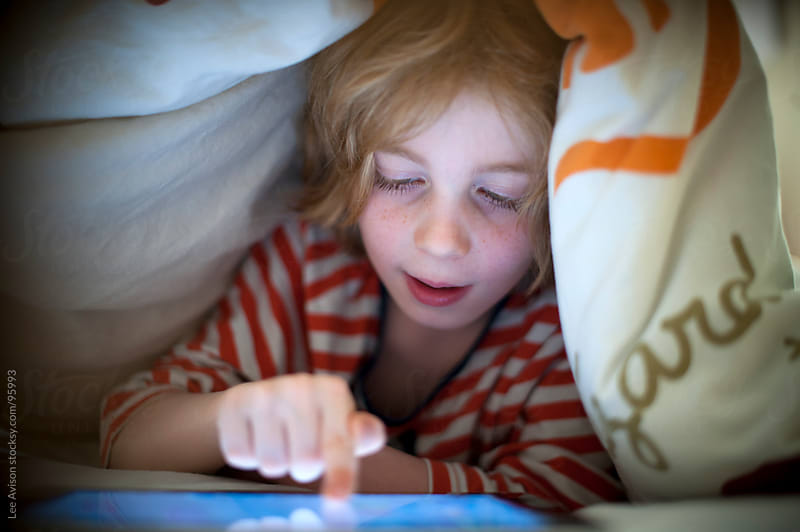 bot using a digital tablet in bed by Lee Avison for Stocksy United