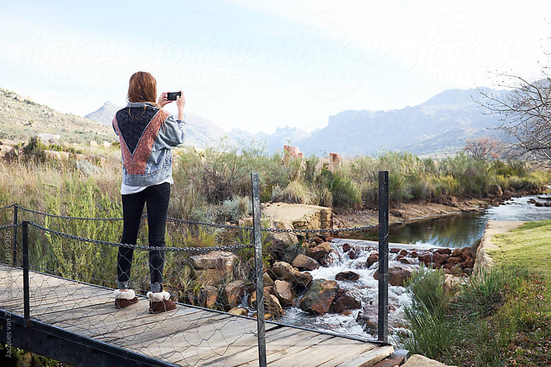 She takes a photograph of a river by Jacques van Zyl for Stocksy United