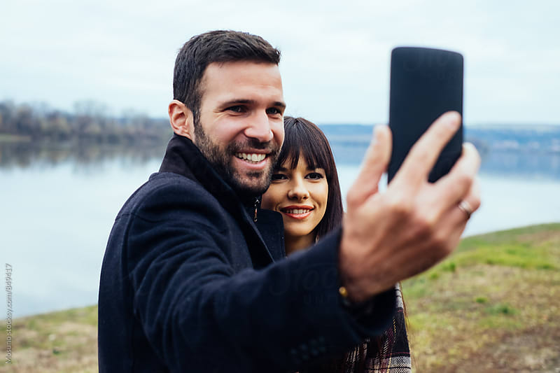 Caucasian Couple Talking Selfie in Nature by Mosuno for Stocksy United