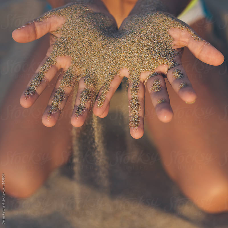 Child's hands playing with sand  by Dejan Ristovski for Stocksy United