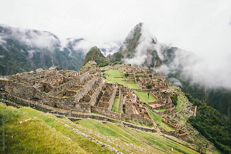 Machu Picchu Inca ancient ruins with clouds in Andes, Peru by Alejandro Moreno de Carlos for Stocksy United
