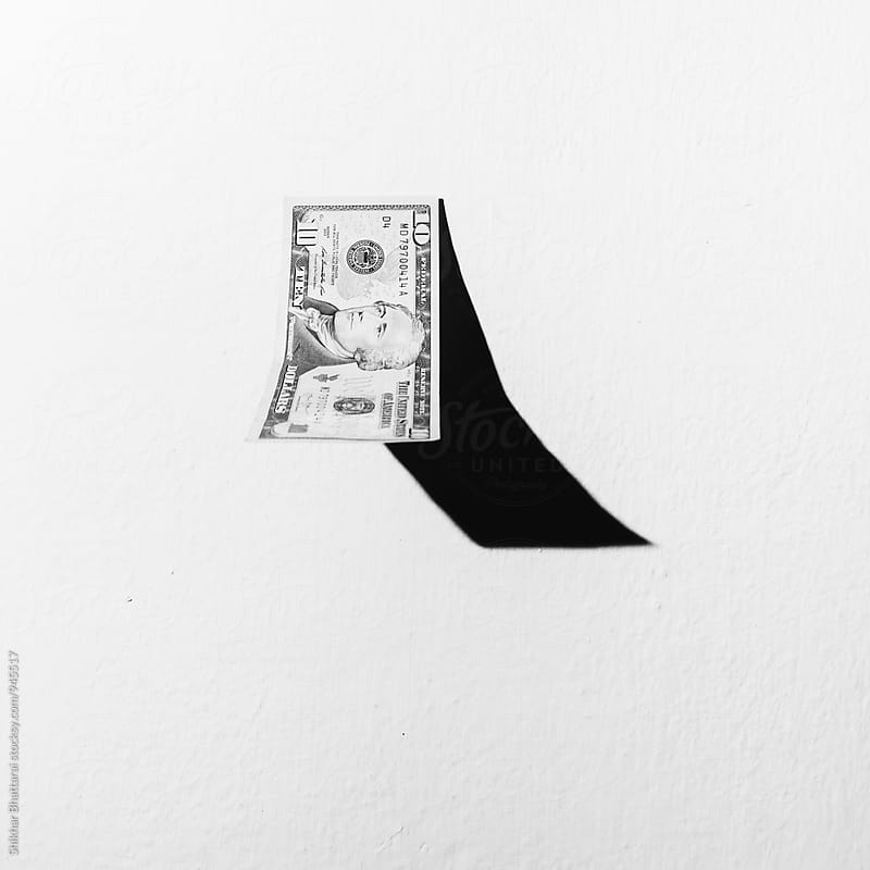 10 dollar bills falling against a white wall. by Shikhar Bhattarai for Stocksy United