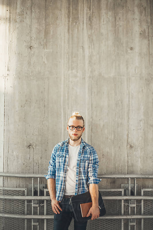 Young Blonde Man standing in front of the wall. by Studio Firma for Stocksy United