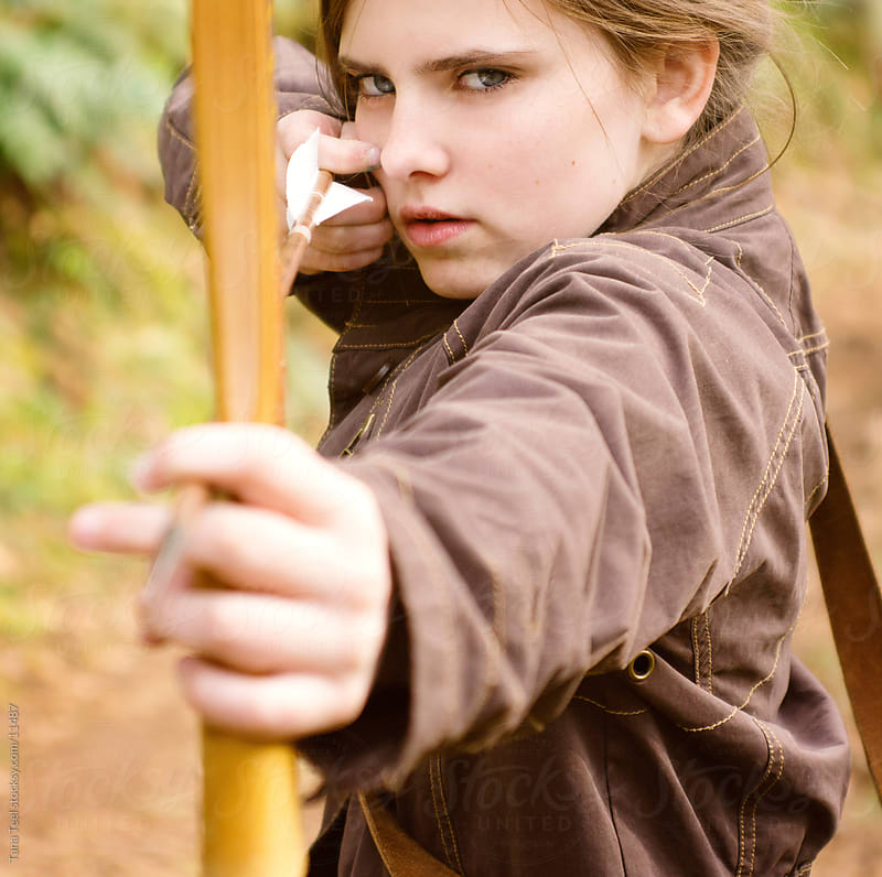 A young girl aims her bow and arrow.  by Tana Teel for Stocksy United