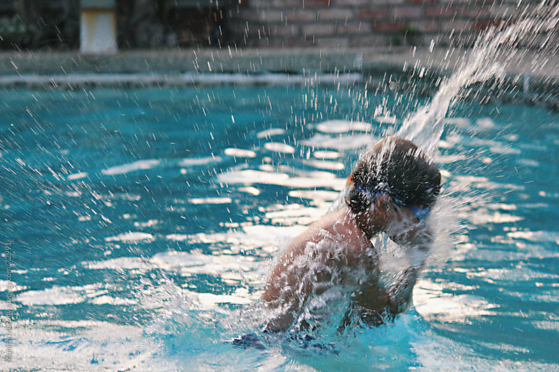Child jumping into swimming pool by Monica Murphy for Stocksy United