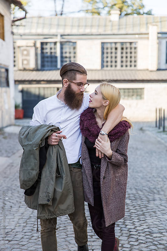 Beautiful young couple walking together on the street by Jovo Jovanovic for Stocksy United