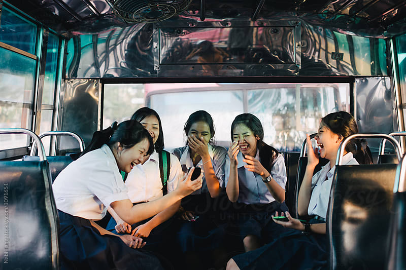 High school students in uniform on the bus in Bangkok by Nabi Tang for Stocksy United