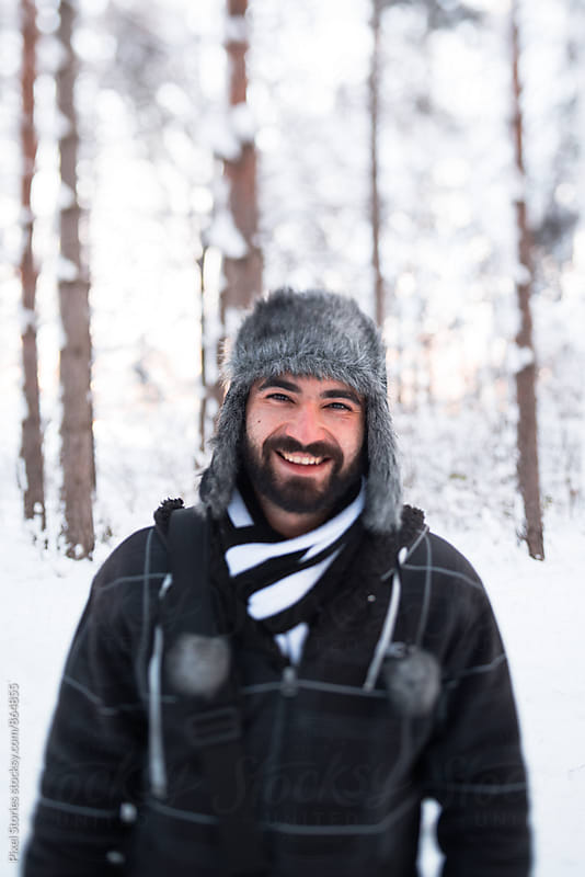 Young man smiling in snowy forest by Pixel Stories for Stocksy United