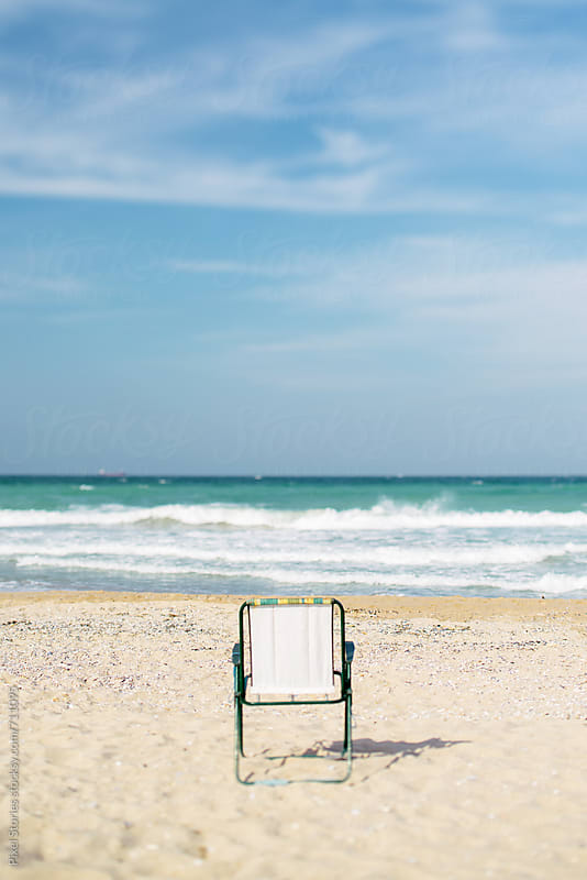Single folding chair on a beach by Pixel Stories for Stocksy United