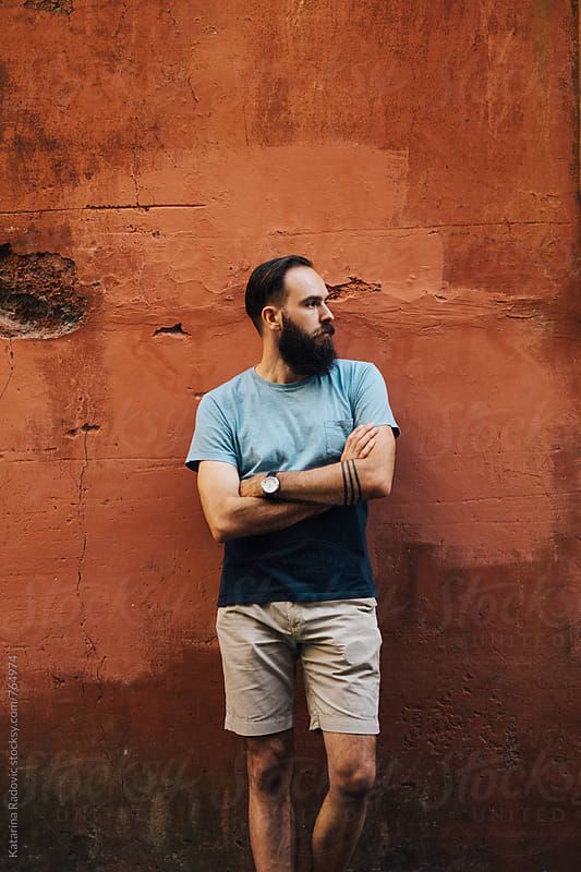 Handsome Bearded Man Posing In Front of the Rustic Wall by Katarina Radovic for Stocksy United