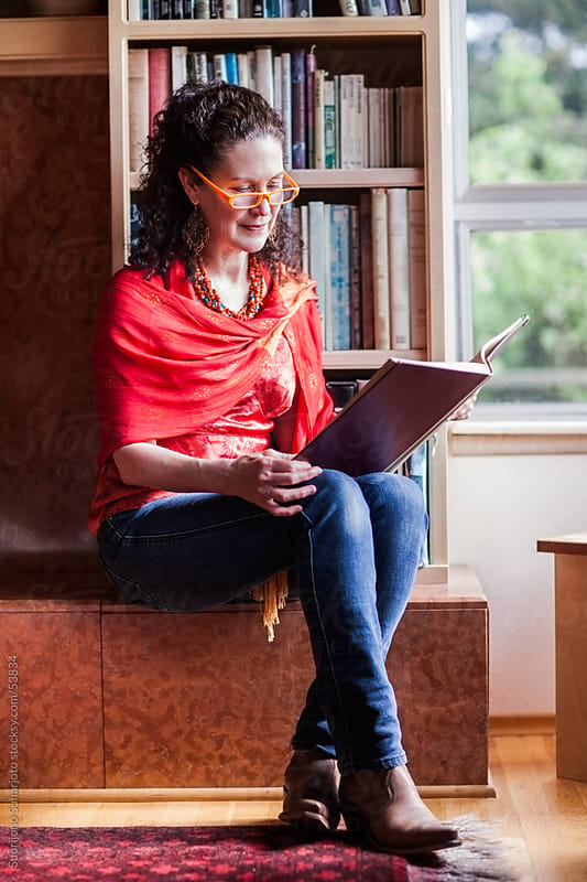 Middle age woman reading a book at home by Suprijono Suharjoto for Stocksy United
