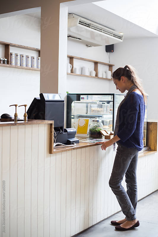 Woman ordering her drink in coffee shop by Jovo Jovanovic for Stocksy United