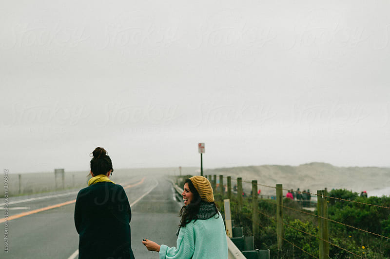 young women walk along roadside next to beach by Jesse Morrow for Stocksy United