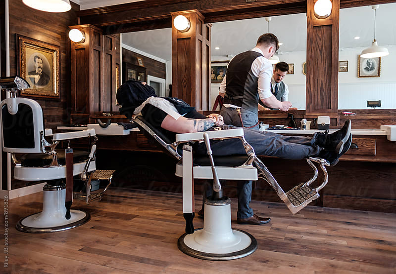 A client reclines in a vintage barber's chair with a warm towel over his face. by Riley J.B. for Stocksy United