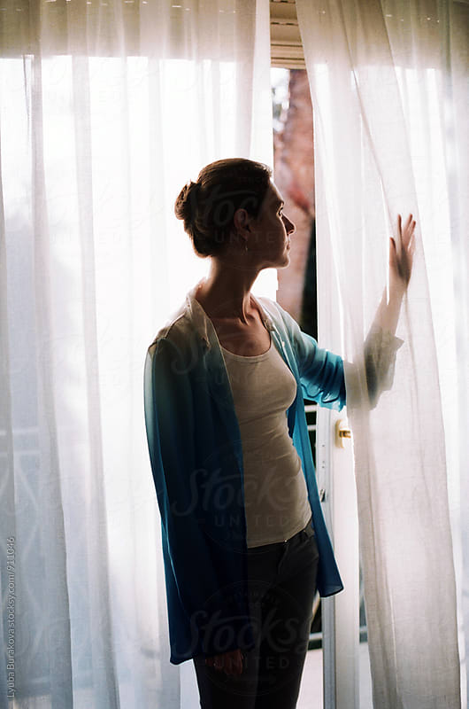 Silhouette of a woman at the window by Lyuba Burakova for Stocksy United
