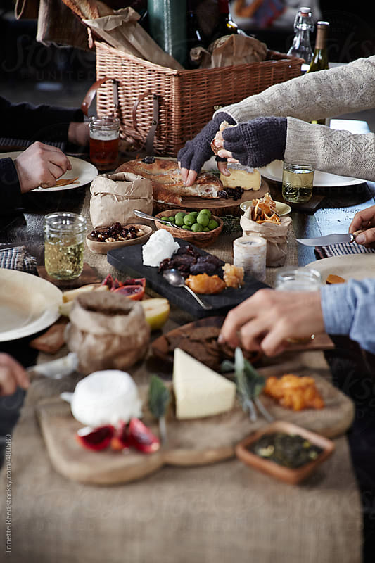 Group of friends enjoying rustic picnic in a barn by Trinette Reed for Stocksy United