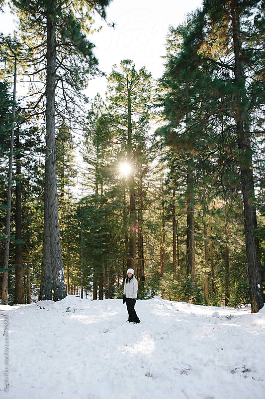 Woman standing on snow on forest's edge by Curtis Kim for Stocksy United