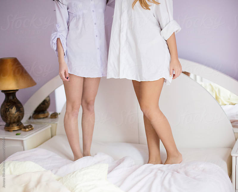 Two female friends standing on bed by Jovana Rikalo for Stocksy United