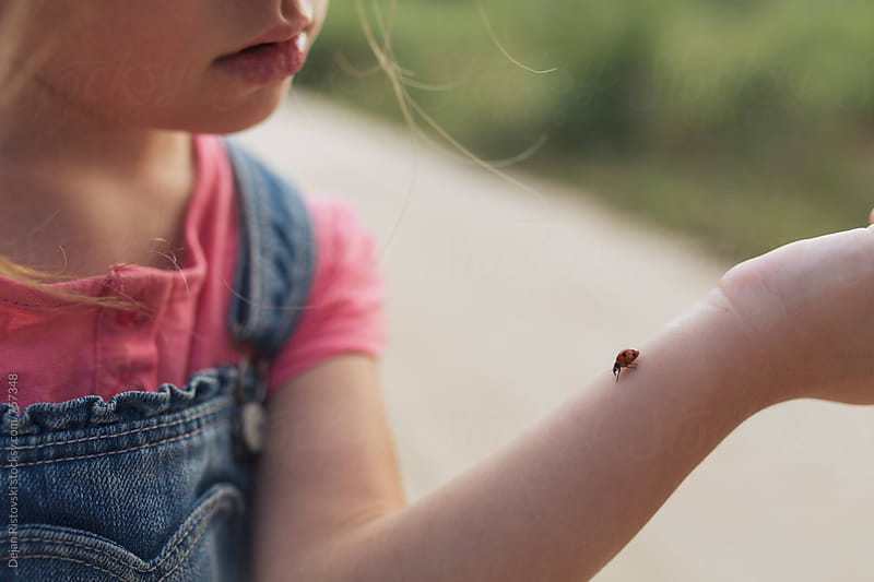Girl and a ladybug. by Dejan Ristovski for Stocksy United