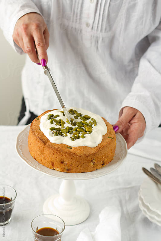 Slicing sponge cake topped with whipped cream and pistachios by Noemi Hauser for Stocksy United