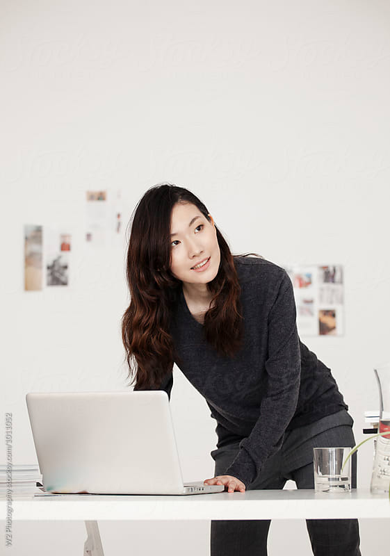 Portrait of an Asian business woman working in her office by W2 Photography for Stocksy United