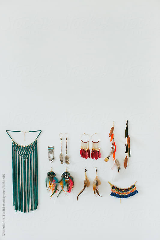 Various Hippie Feather Earrings Hanging on White Wall by Julien L. Balmer for Stocksy United