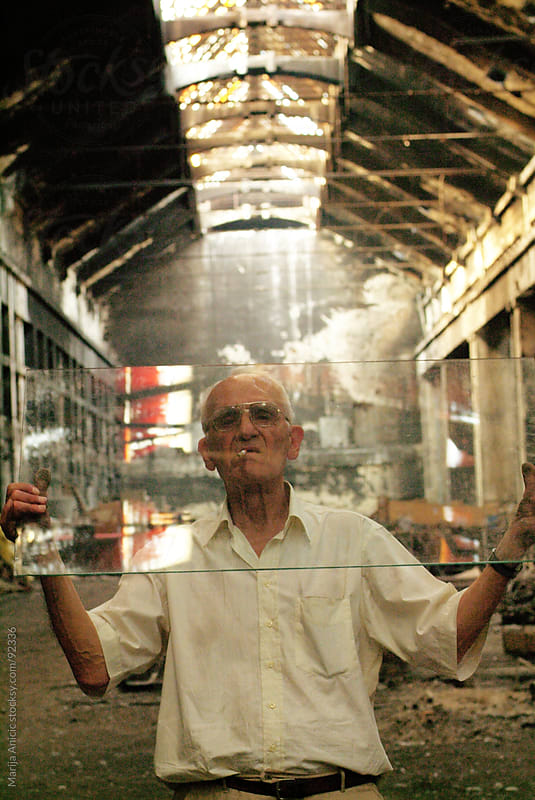 old man holding big piece of glass in abandoned space by Marija Anicic for Stocksy United