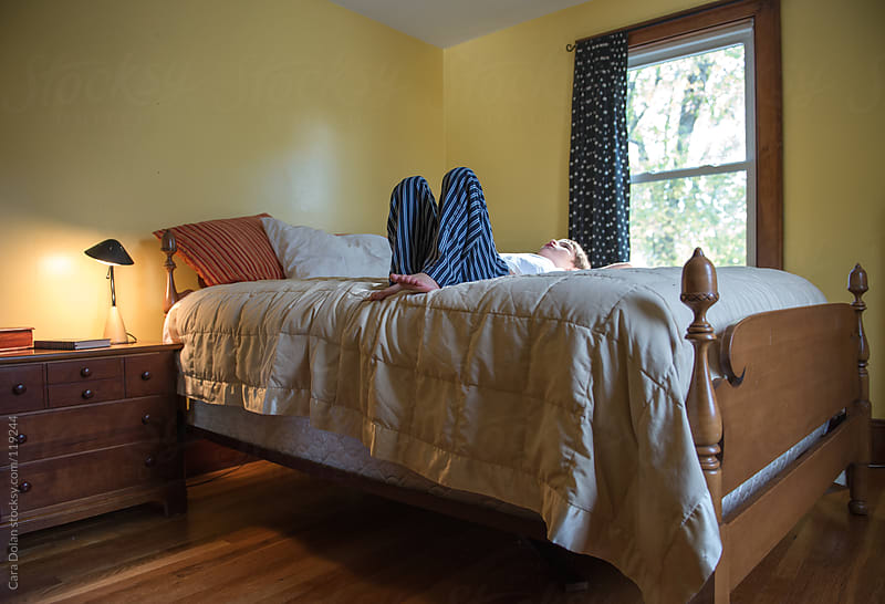 Boy lies on his back on his bed, staring at the ceiling by Cara Dolan for Stocksy United