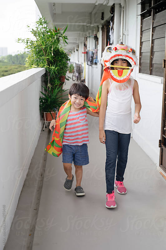 Two kids walking at typical Singapore HDB flat corridor by Alita Ong for Stocksy United