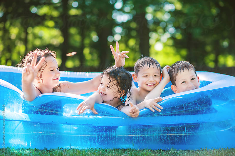 Children having fun in an inflatable pool by Lea Csontos for Stocksy United