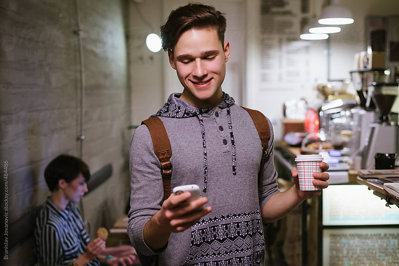 Young man holding take out coffee and phone in a coffee shop by Brkati Krokodil for Stocksy United
